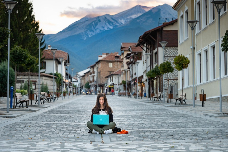 Woman working on laptop in the street